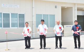 テープカットで県内初の複合型施設完成を祝った石垣市水産加工施設の落成式=15日午後、同施設前