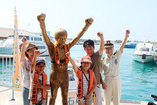 救命胴衣を着せられた具志堅用高の銅像と記念撮影をする観光客ら=16日午前、同離島ターミナル