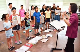 対馬丸記念館で行われる平和コンサートに向け、練習に励むいしがき少年少女合唱団の団員ら=18日午後、石垣市立文化会館
