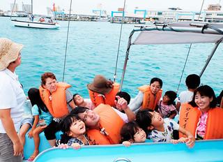 ヨットセーリングで高さ12㍍の高さまで上っていく帆に歓声を上げる親子連れら=20日午後、石垣港