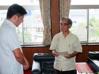中山義隆市長に中間報告を行う川平永光委員長(右)=21日午後、市長室
