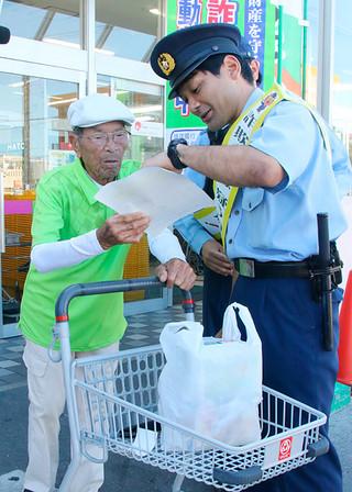 チラシを配り還付金詐欺に注意を呼びかける八重山署の署員=24日午後、市内スーパー