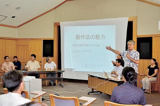 琉球大学公開講座で動作法の魅力について紹介する同大の金城昇教授(正面右)ら=7月31日午後、市立図書館視聴覚室