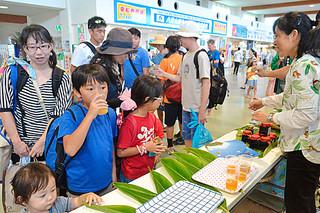 パインジュースなど島々の特産品を堪能する観光客ら=1日午後、石垣港離島ターミナル