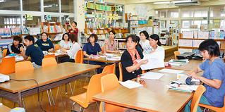石垣小学校の校内研修で、仲松久弥教諭の説明に聞き入る教諭ら=7月27日午前、同校図書室