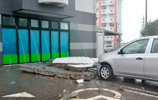 ホテルの外壁が崩れ落ち、敷地内駐車場に止めてあったレンタカーのフロント部分が破損した=7日午後、市内八島町