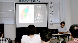 官元瑜氏(右側こちら向き)が映像を使いながら台湾の原住民について解説した講演会=7月30日、町複合型施設