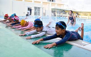 夏休み水泳教室でバタ足の練習をする児童たち=10日夕、平真小学校プール