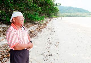 決死隊が到着した海岸で、70年前の偉業に思いを巡らせる金城珍良さん=14日午前、川平底地