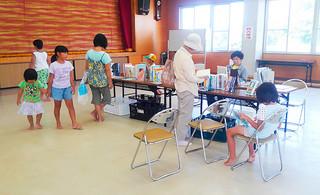 川平公民館で行われた移動図書館で、本に親しむ地域住民ら=5日午後、同館(市立図書館提供)
