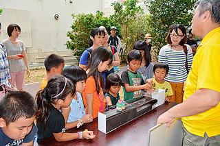 石垣市「親と子のお天気教室」で、津波実験に見入る子どもたち=16日午後、市健康福祉センター
