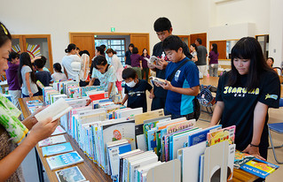 初開催の夕涼み移動図書館で、本に見入る子どもたち=15日夕、伊原間公民館