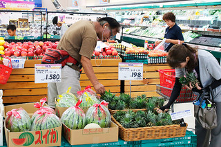 旧盆用品の果物を買い求める客ら=25日午後、マックスバリュやいま店