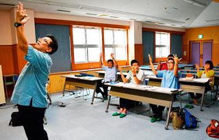 県立総合教育センターの宜保康研究主事(左)から指を使ったかけ算九九の仕方などを学ぶ宮良小学校の教員ら=25日午後、市健康福祉センター視聴覚室