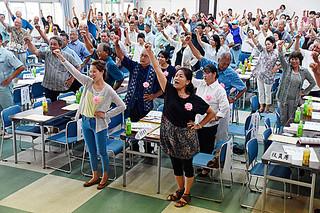 生産者大会で「頑張ろう」を三唱して生産拡大と品質の向上に向けて気勢を上げる会員ら=4日午後、大浜公民館
