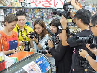 知念秀子常務から人気の「オニササ」について取材する台湾のメディア関係者ら=7日午前、字登野城の知念商会本店