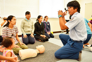 市消防の真栄田義史救急救命士(右)から心肺蘇生法について説明を聞く応急手当て講習会の参加者=9日午後、市消防本部2階会議室