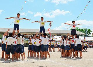「The シンクロ」で息の合った組体操を披露した石垣小学校の5、6年生=13日午後、同校