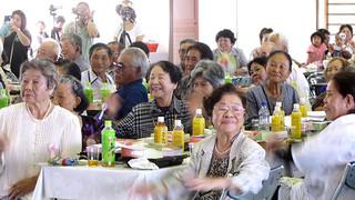 与那国町の敬老会で余興を楽しむお年寄りたち=15日、与那国中学校体育館