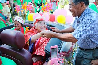 カジマヤーのパレードで祝福を受ける宮良貞さん=20日午前、石垣市川平