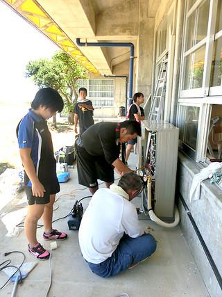 クーラーを設置する吉田幸治さん(中央の黒いシャツの男性)と、手伝いをする久部良中学校の生徒たち=7月31日、同校