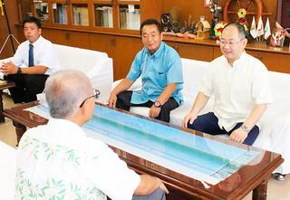 渡久山修校長(手前)に学科の内容を説明する江口文陽教授(右)。左は日健総本社の森伸夫代表取締役社長=15日午前、校長室