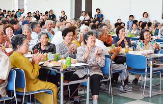 大浜公民館の敬老祝賀会で、多彩な余興に見入り、拍手を送る高齢者たち=23日午後、同館