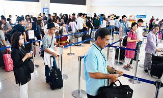 シルバーウイークで訪れたUターン客で混み合う航空カウンター前の手荷物検査場=23日午前、南ぬ島石垣空港