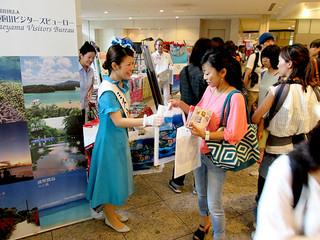 来場者にパンフレットを配布して八重山観光をPRするミス南十字星の大泊祥子さん=21日午後、クイーンズスクエア横浜(YVB提供)