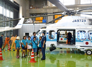 「空の日」と「空の旬間」にちなむイベントで海上保安庁のヘリコプターを見学する子どもたち=26日午前、第11管区海上保安本部石垣航空基地