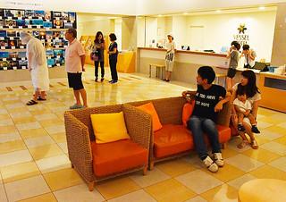 台風21号の影響でホテル内に缶詰めとなり、ロビーから外の様子をうかがう宿泊客=28日午後、ベッセルホテル石垣島
