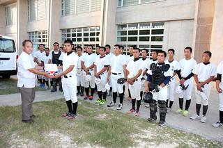 県高校野球秋季大会で決勝進出を果たし、九州高校野球大会に出場する八重高野球部にボールを贈る34オールスターズ=7日夕、市中央運動公園