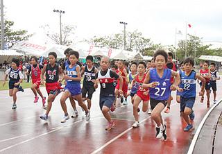26競技に延べ867選手が出場した第15回地区小学校陸上競技大会。大会最初の種目の代表男子1000㍍でわれ先にとコーナーへ飛び出す選手たち=10日午前、市中央運動公園陸上競技場