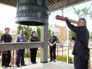 十・十空襲犠牲者を追悼し、世界平和の鐘を打ち鳴らす人たち=10日午後、新栄公園内