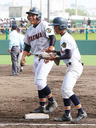 3回裏、右前打で出塁し、笑顔でベンチに応える八重高の東盛隼己=11日午後、沖縄セルラースタジアム那覇
