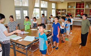 クラブ活動「英会話」の時間に英語版の校歌を歌う大本小学校の児童たち。右は英訳した漢那ひとみ校長=9日午後、同校
