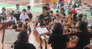 日本センチュリー交響楽団の団員を前に、指揮者の体験をする波照間小中学校の慶田本碧君=27日、同校