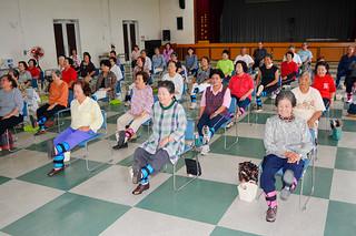写真説明=地域づくりによる介護予防推進モデル事業の交流会で、笑顔で「いきいき百歳体操」を行う参加者たち=30日午後、大浜公民館