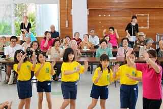 演奏後、大川婦人会の女性と一緒に踊りを披露する登野城小器楽クラブの児童ら=10月31日午前、大川公民館