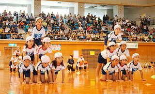 運動会に代わる体育学習発表会で組体操を披露する登野城小の1、2年生=1日午前、石垣市総合体育館