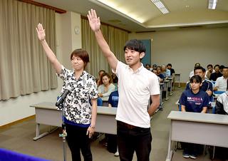 選手宣誓を行うバドミントン代表の川満起史選手(右)と吉本奈美選手=9日夜、大浜信泉記念館会議室