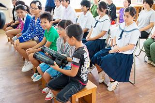 高倉健さんから贈られた双眼鏡を手にする児童ら=10日午前、富野小中学校