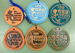 大浜工房がこれまでにつくった完走記念メダル。右下が第14回大会のサンプル