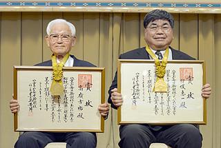 八重山毎日文化賞の正賞を受賞した髙嶺方祐氏(左)と狩俣恵一氏=21日午前、南の美ら花ホテルミヤヒラ