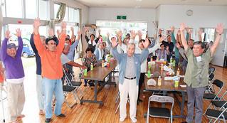 竹富町役場の位置を問う住民投票の結果が西表大原に決まり、万歳をして喜ぶ住民=11月30日午後、大原公民館