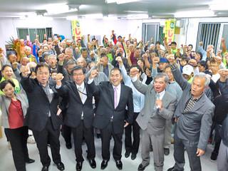 「団結して頑張ろう」と気勢を上げる支持者たち=13日夜、真栄里公園北側の事務所