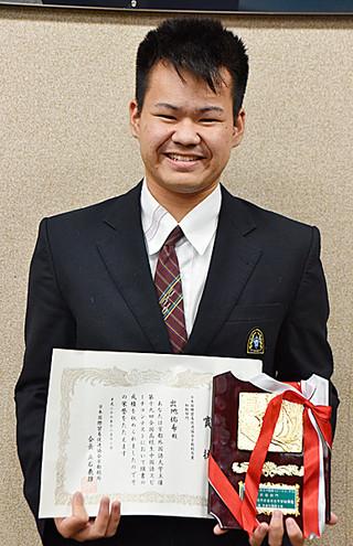 全国高校生中国語スピーチコンテストで日本国際貿易促進協会京都総局賞を受賞した八商工の出地佑希君=15日午後、八重山商工校長室