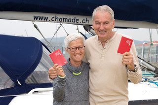 スイスのパスポートを手に「シャマド」号の前に立つマーク・デコッレさん(右)とシルヴィ・コーエンさん=16日午後、浜崎町のヨットハーバー