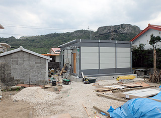 設置作業が行われている全壊世帯を対象にした仮設住宅=17日午後、祖納集落