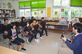 県立芸大の沢岻安優さん(右)から三線を学ぶ参加者たち=19日午後、竹富小中